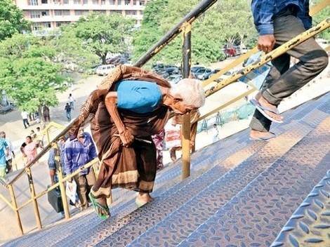 Elderly woman struggling to climb steep pedestrian bridge