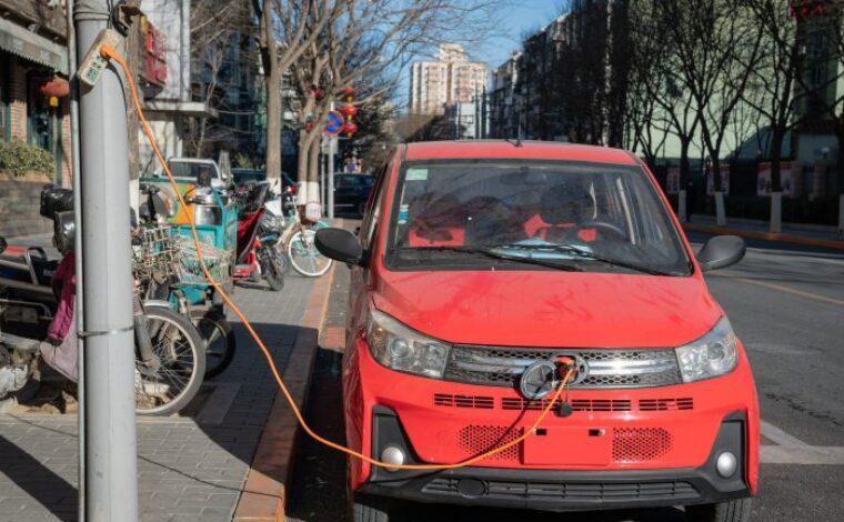 A tiny car is plugged in to charge by the side of a street  in Beijing, China on January 4, 2021.